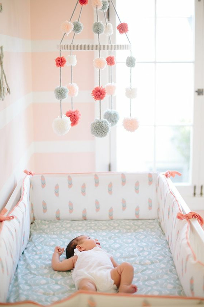 babyzimmer grau rosa spielzeug fliegt über dem baby bunte fell bälle deko schlafendes baby