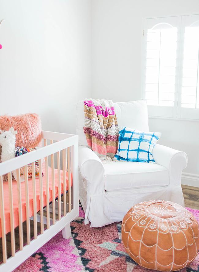 babyzimmer mädchen. ideen, weißes interieur mit lila und rosa dekorationen, babybett, sessel und bodenkissen