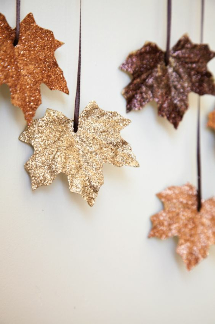 wanddeko selber machen, baumblätter dekoriert mit glitzer, braune schleife, herbstdeko