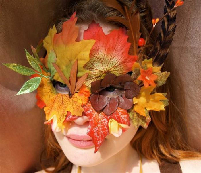 mädchen, maske aus baumblättern, feder, blönde haare, braune augen