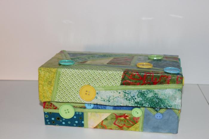 Basteln mit Karton - ein Collage aus Geschenkpapier und Knöpfen auf dem Karton