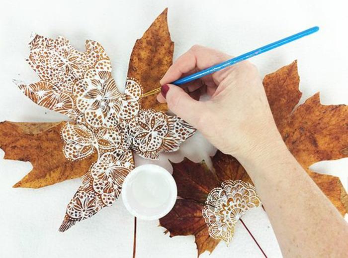 basteln herbst, große getrocknete baumblätter mit weißer farbe bemalen, pinsel, zeichnung