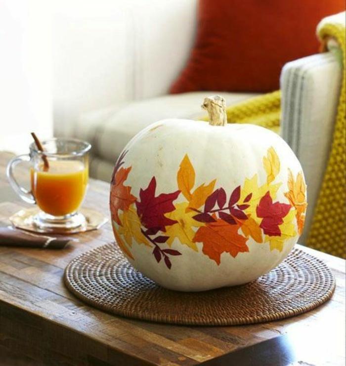 weißer kürbis dekoriert mit getrockneten blättern, tischdeko, orangensaft, glas, tisch