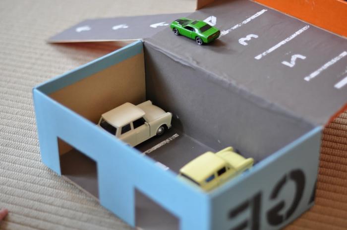 Spielautos in Garage in blauer Farbe in zwei Stöcke - Basteln mit Karton