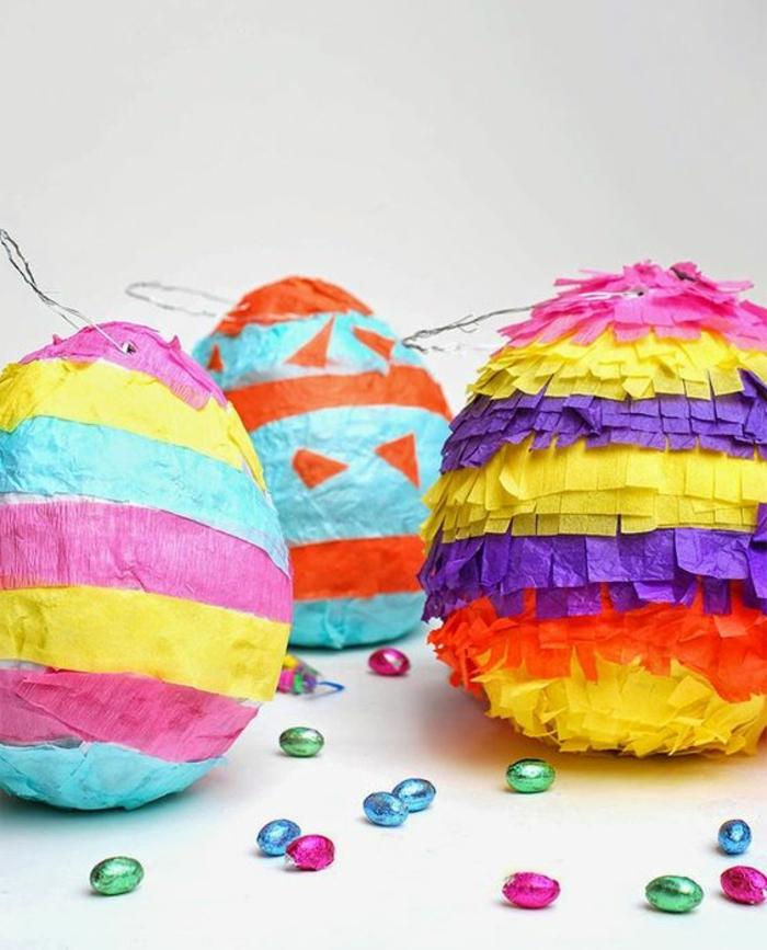 pinata basteln - große eier aus pappe dekoriert mit buntes papier, bonbons