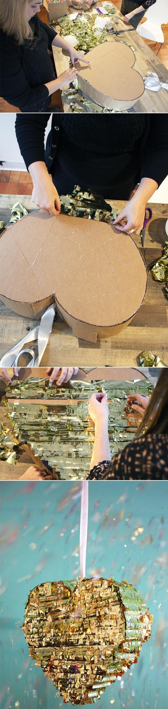 pinata in form von einem herzen mit goldenem papier verzieren