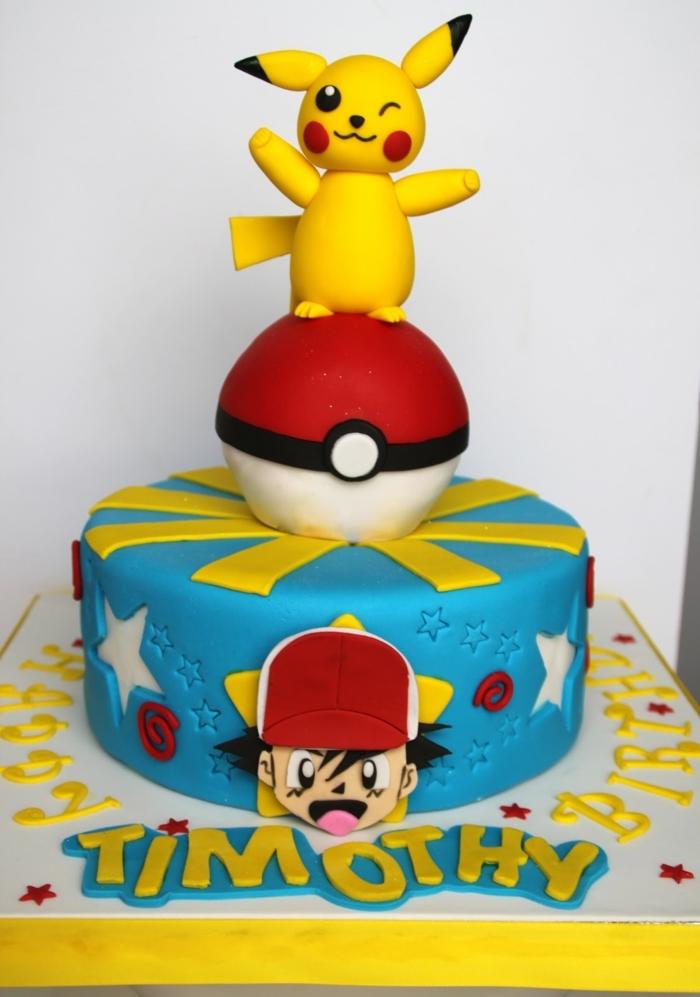 idee für eine blaue pokemon torte - ein kleines pokemon wesen pikachu mit schwarzen augen und roten backen und ein roter pokeball und ein junge mit mütze