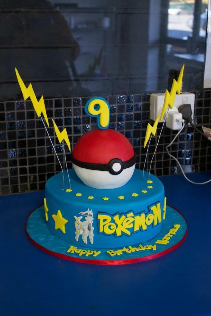eine tolle blaue pokemon torte mit rotem pokeball und zwei gelben blitzen und gelben sternen und einer gelben überschrift