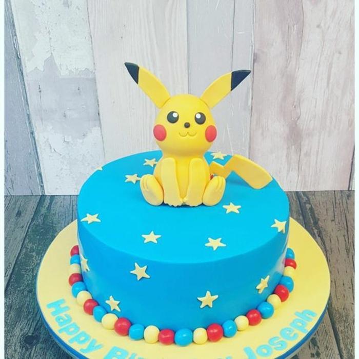 hier zeigen wir ihnen eine unserer ideen für eine blaue pokemon torte mit einem gelben pokemon wesen mit gelben sternen und gelben, riten und blauen pralinen