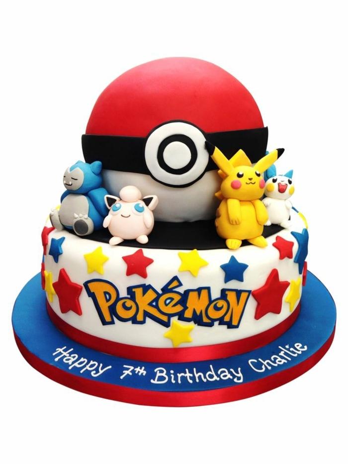 idee für eine schöne zweistockige weiße pokemon torte für kinder - mit einem großen roten pokeball, roten. blauen, gelben sternen. einer gelben überschrift. vier kleinen pokemon wesen, einem gelben pikachu
