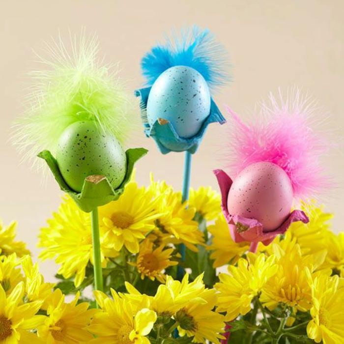 drei Eierbecher in verschiedene Farben mit Feder - rosa, blau und grün