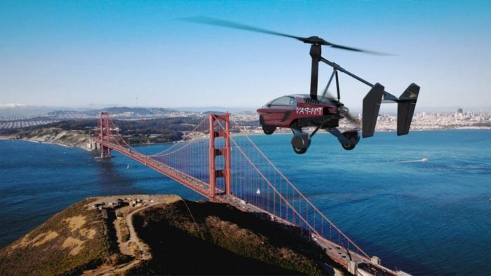 pal-v - ein rotes fliegendes auto mut schwarzen propellern und das brücke über das goldene tor