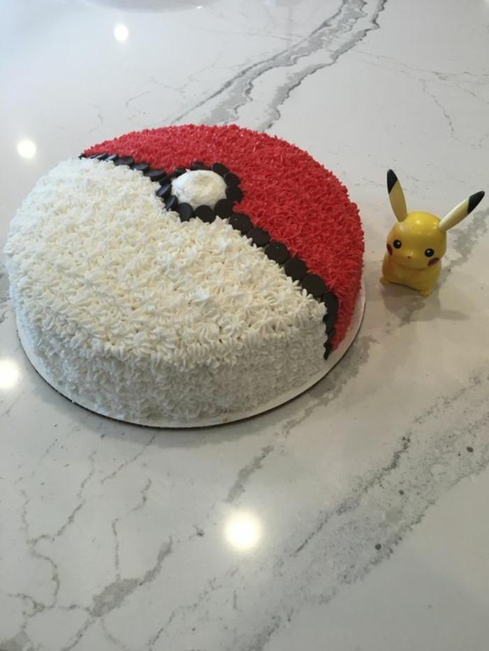 leckere pokemon torte, die wie in pokeball ausseieht - mit schwarzer, weißer und roter creme, und ein kleines gelbes pikachu
