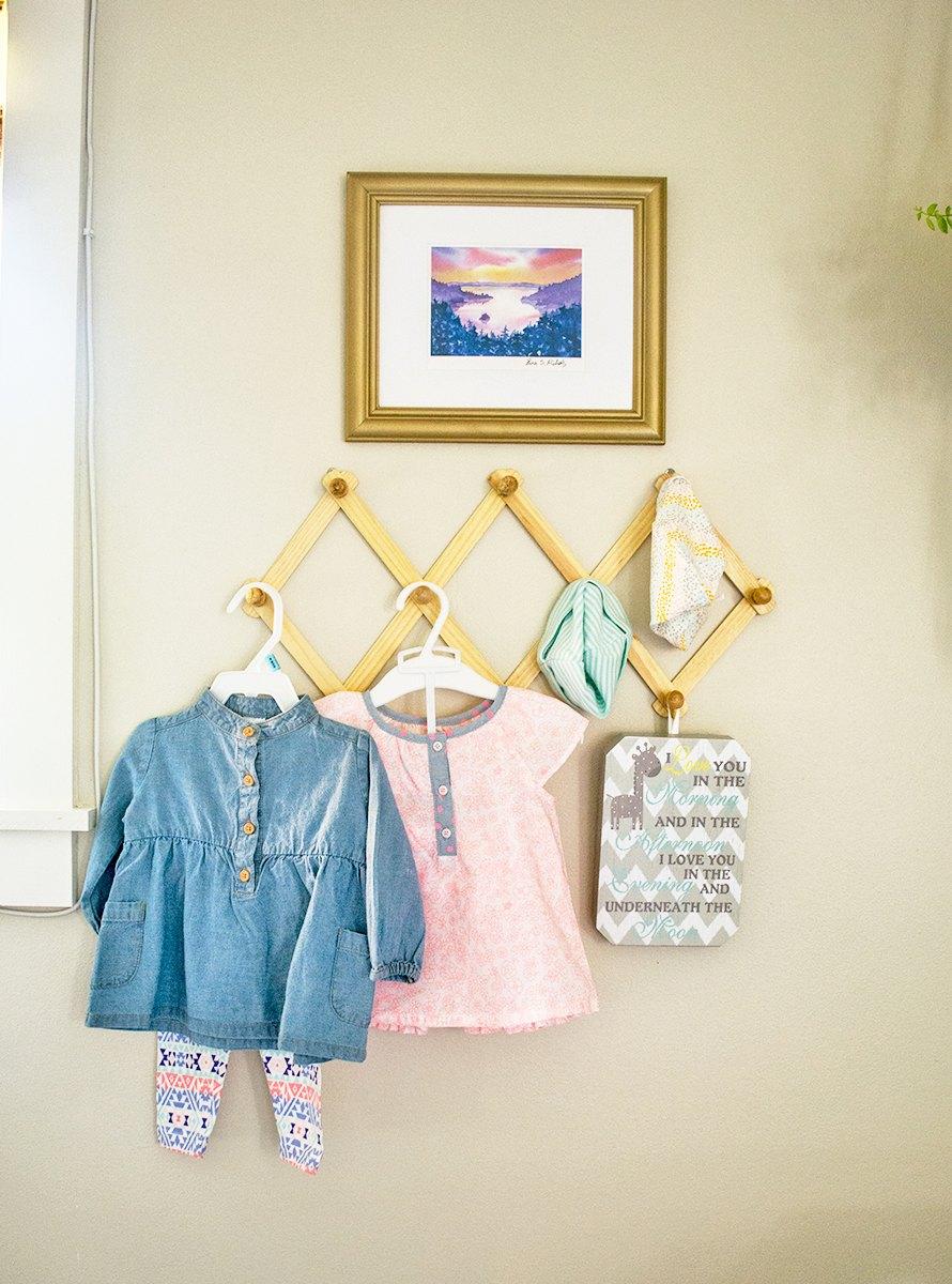 kinderzimmer mädchen ideen zum dekorieren und einrichten, kleiderhaken mit babykleidung angehängt, wanddeko bild an der wand
