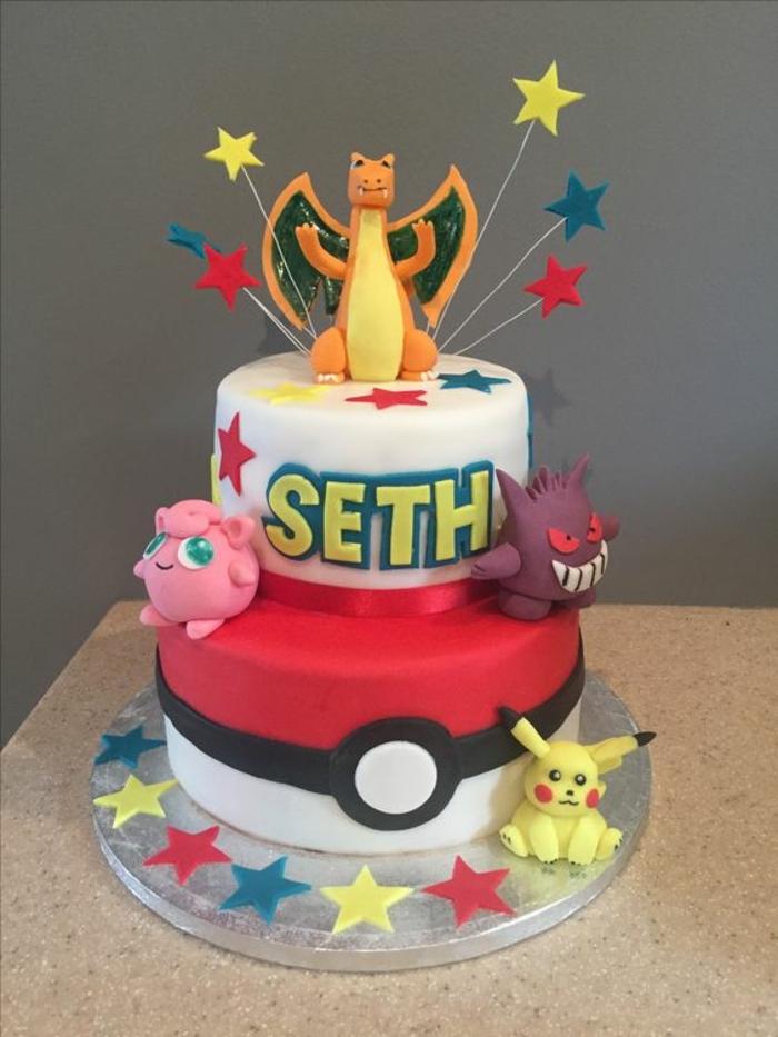 idee für eine leckere zweistockige pokemon torte mit pokemon wesen, drachen pokemon, roten sternen, einem gelben pikachu. einem roten pokeball und dragon pokemon
