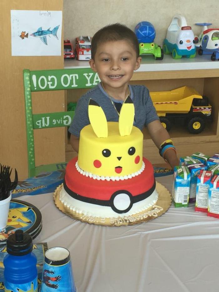 hier ist kind mit einer zweistöckigen torte - ein gelbes pokemon wesen pikachu und ein roter pokeball