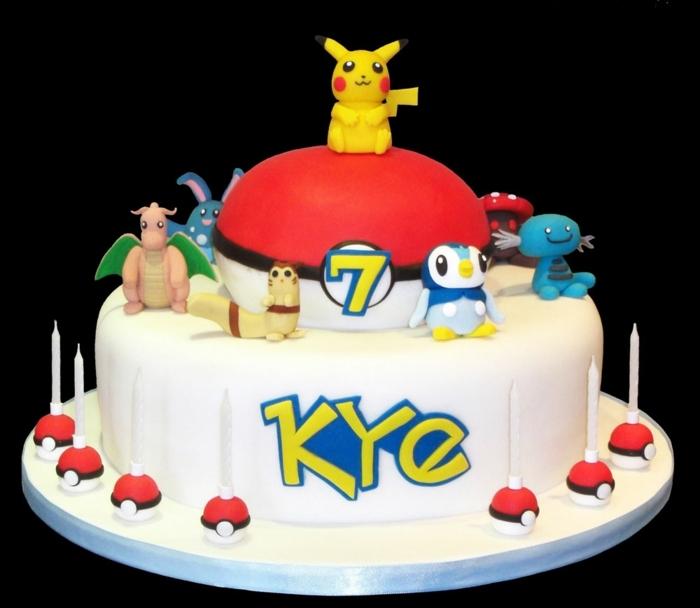 weiße pokemon torte mit weißen kerzen, kleinen pokebällen, einem gelben pikachu und verschiedenen pokemon wesen, drachen pokemon