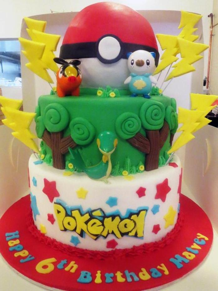 zweistockige pokemon torte mit grünen bäumen, schlange, gelben blitzen und einem roten pokeball