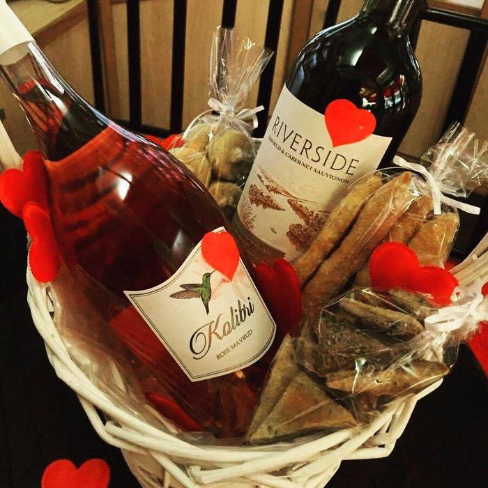 geschenkkorb mit zwei weinflaschen, rotwein und rose, suessigkeiten