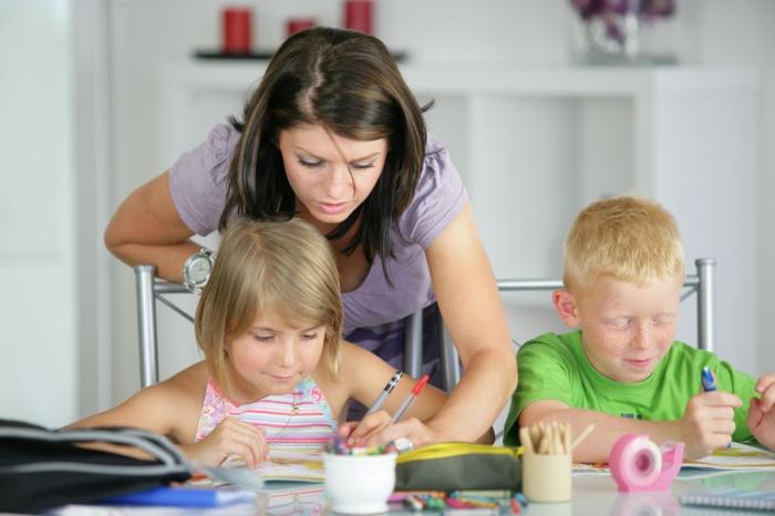 Hauspersonal für Kinderbetreuung, Kinderlehrerin, die Kindern mit ihren Hausaufgaben hilft