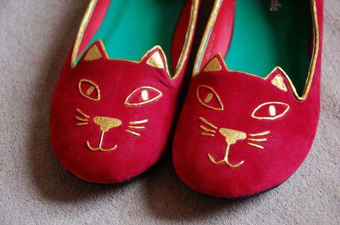 rote Schuhe nähen mit einer goldenen Verzierung wie eine Katze Miene