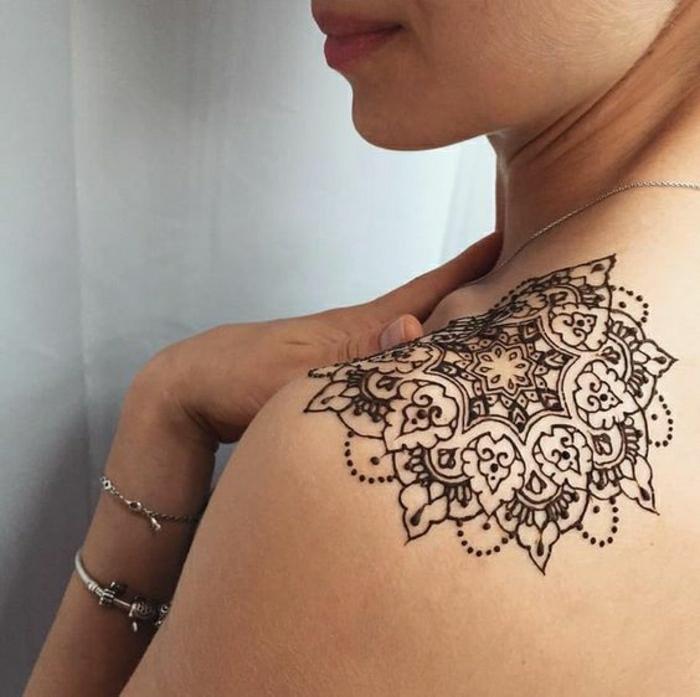 Frau mit Schultertattoo aus Hennafarbe, Mandalatattoo in schwarzer Farbe, silberne Armbänder