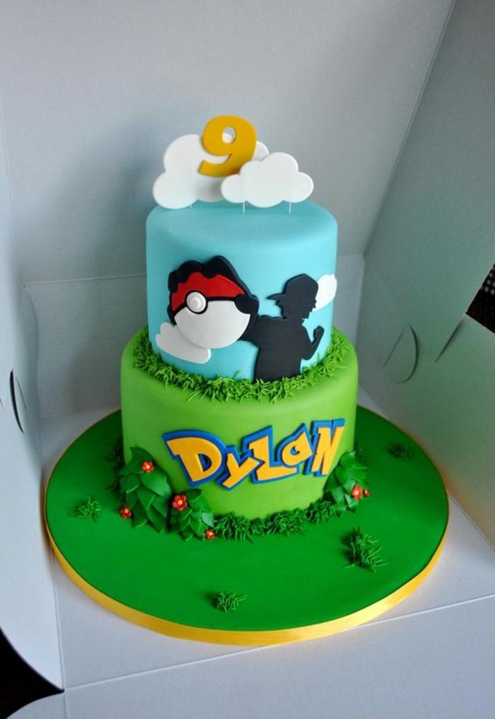 zweistöckige pokemon torte mit wolken, blumen und einem roten pokeball und grass