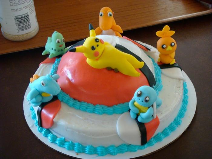 ein roter pokeball und sechs kleine pokemon wesen, ein pikachu - eine idee für eine pokemon torte mit einer blauen creme