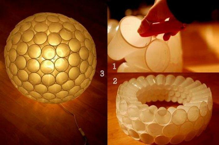 ein Lampenschirm mit ganz einfachem Design aus Plastikbechern in weißer Farbe, Kugelform