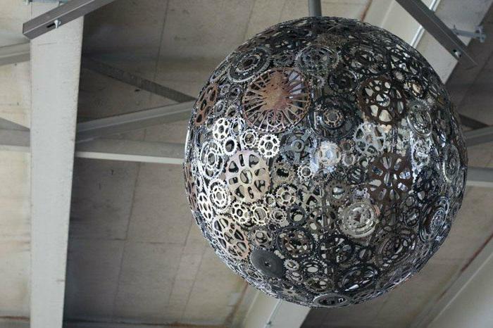 Lampenschirm aus metallen Bewegungsmechanismen in unterschiedlicher Grölße, spärische Form