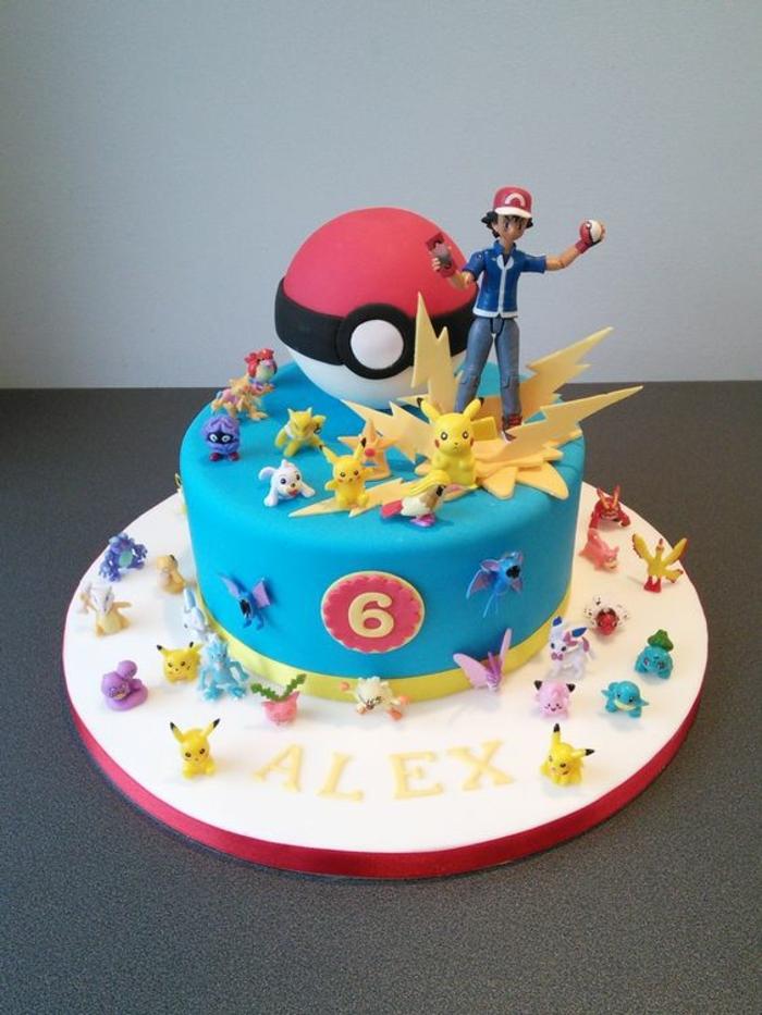 eine blaue pokemon torte mit gelben blitzen, einem roten pokeball, kleinen verschiedenen pokemon wesen, pikachu, junge mit einer roten mütze