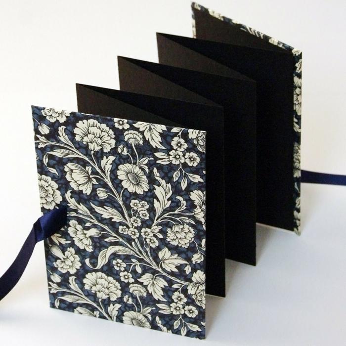 schwarze Blätter und ein Umschlag mit weißen Blumen, schwarzes Band