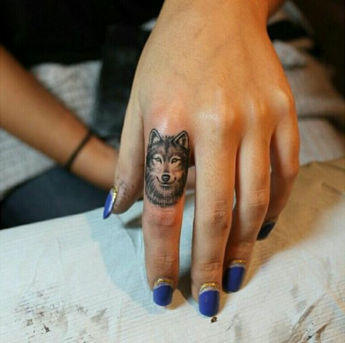 eine unserer lieblingsideen für einen wolftattoo - wolf tattoo auf dem finger und lila nagellack