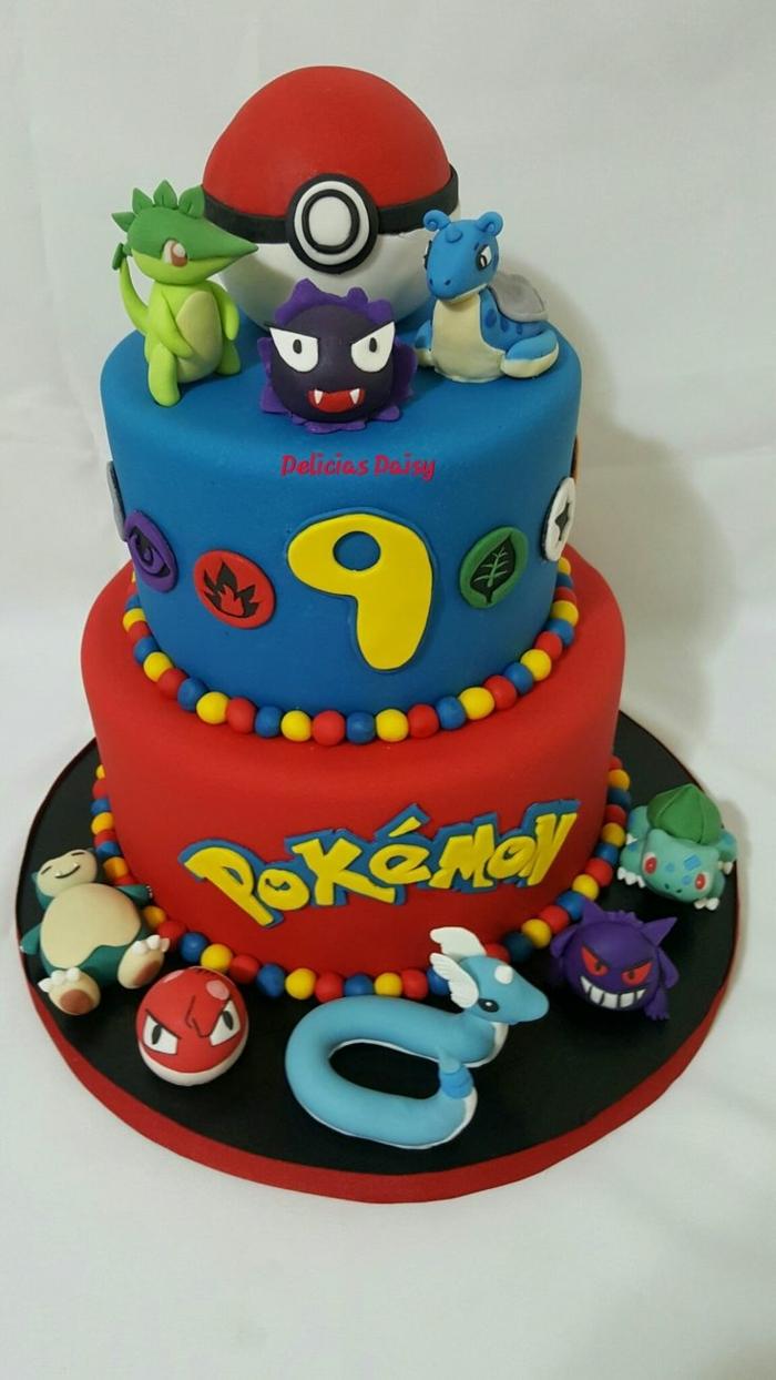 zweistöckige torte - hier ist eine tolle idee mit kleinen pokemon wesen, einem roten pokeball, gelben überschriften, pralinen