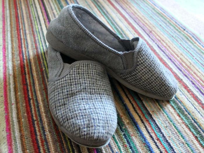 graue Schuhe mit kleinen Sternen bemustert auf gestreiften Hintergrund