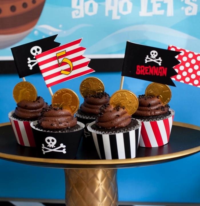 Cupcakes aus Schokolade mit kleinen Totenkopf Fahnen und Münzen wie aus einem Schatz