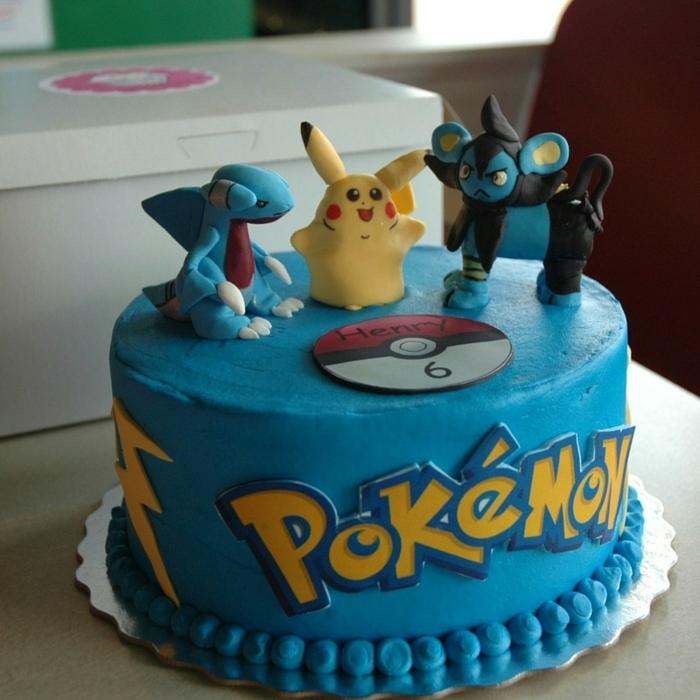 eine blaue pokemon torte mit einem roten pokeball und drei kleinen pokemon wesen und eine gelbe überschrift