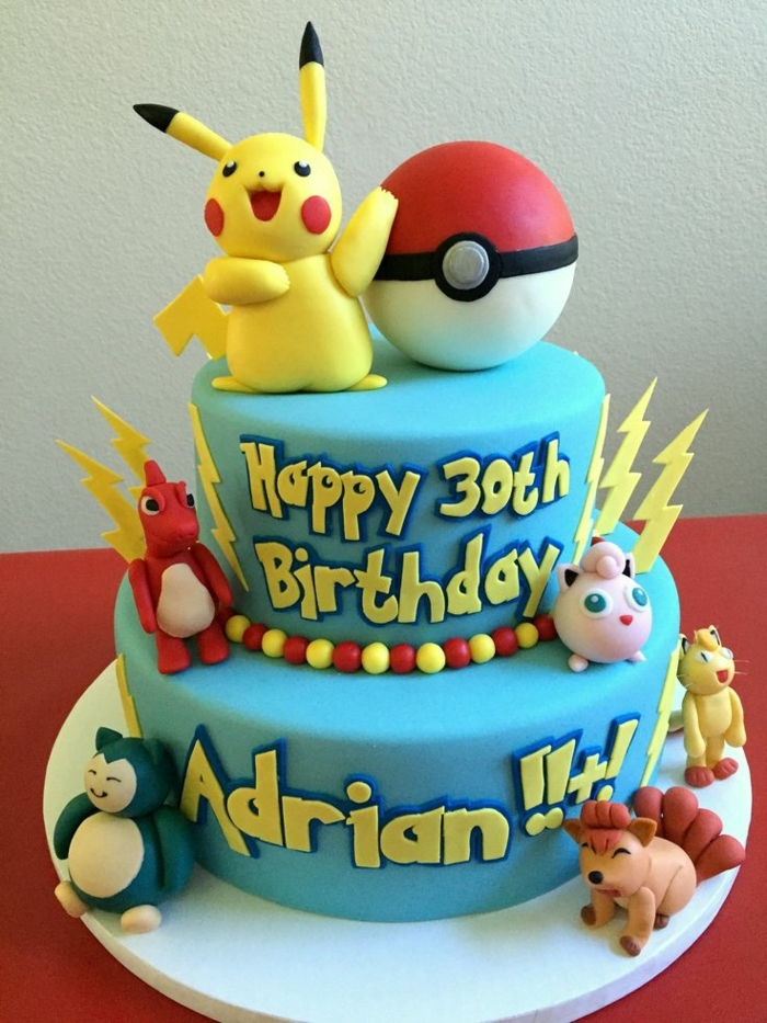 eine blaue zweistöckige pokemon torte - ein gelbes pikachu mit roten backen, ein roter pokeball, pokemon fuchs, drachen pokemon, dragon pokemon, gelbe blitze