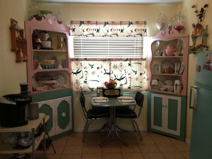 Rockabilly Deko - Fensterdeko, Gardinen mit abstraktem Muster, zwei Küchenschränken in den Ecken, kleiner Zweisitzer Tisch