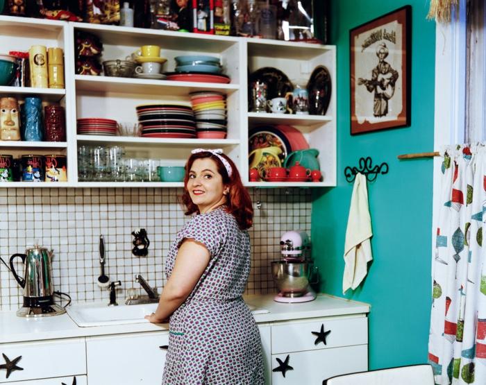Retro Deko in der Küche - viele Teller, Wandbild, blau gestrichene Wände, eine Frau mit Kleid aus 50er