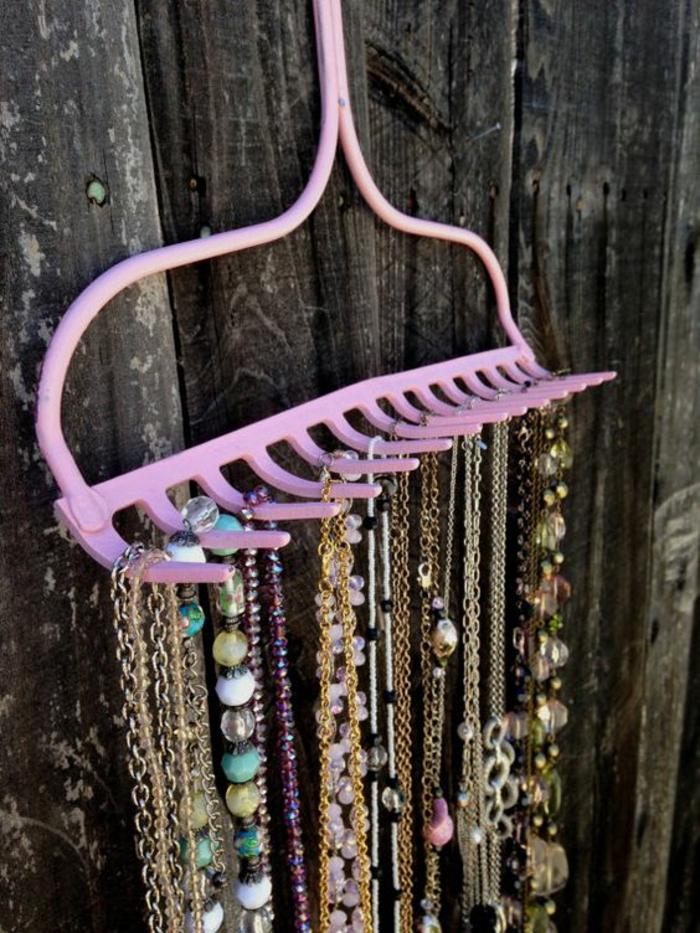 rosa kettenständer, viele goldenen halsketten mit kristallen