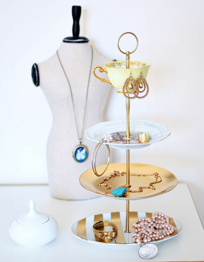 schmuckaufbewahrung aus tellern, kaffeetasse, ohrringe, goldene halskette, perlenkette