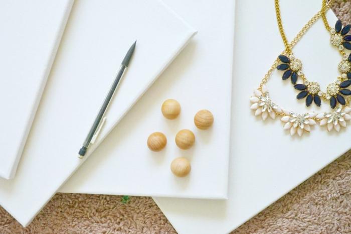 weiße leinwände, bleistift, möbelknöpfe aus holz, goldene halsketten
