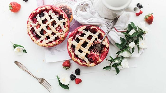 DIY Süßwaren verkaufen - zwei Kuchen mit frischen roten Früchten, Pflanzendeko, goldene Gabel, weißer Tuch