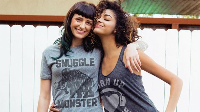 Selbstgemachtes verkaufen - zwei junge Frauen mit T-Shirts mit Print umarmen sich vor einem weißen Zaun