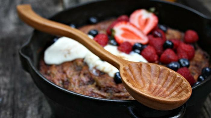 Handarbeiten verkaufen, ein schwarzer Keramiktopf mit Kuchen und frischen roten Früchten, Sahne, Holzlöffel