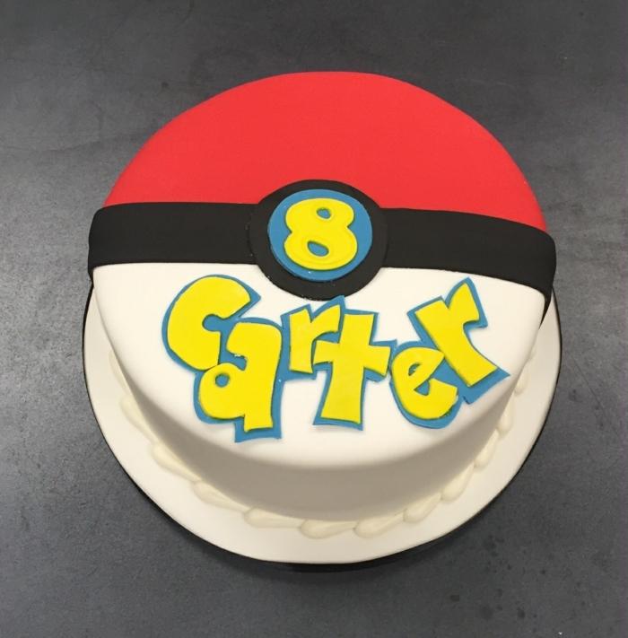 rote pokemon torte für kinder mit gelben überschriften - sie sieht wie ein pokeball aus