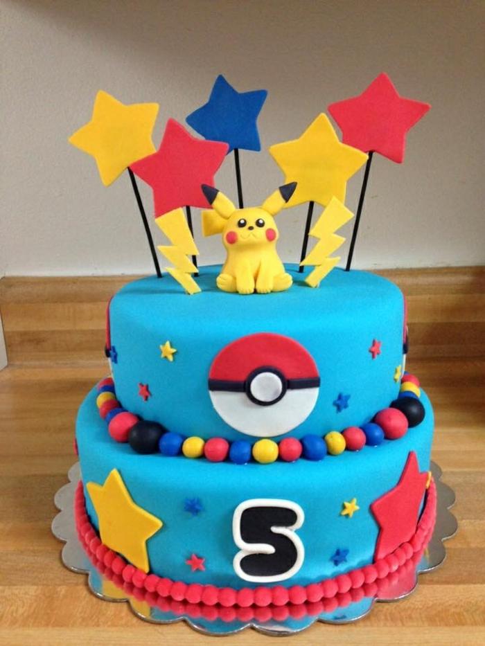 eine zweistöckige blaue pokemon torte für kinder - mit gelben blitzen, einem gelben pokemon wesen pikachu, roten, gelben und blauen sternen, pralinen und einem roten pokeball