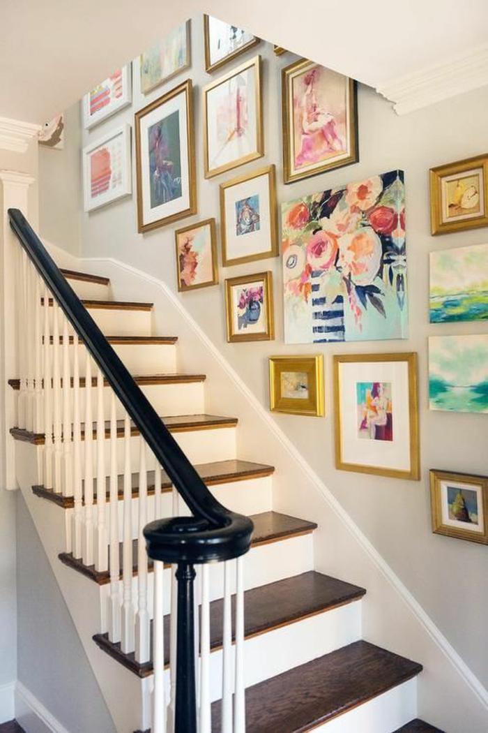 goldene Rahmen, bunte Bilder, schwarzes Geländer weiße und braune Treppen - Treopenaufgang Deko