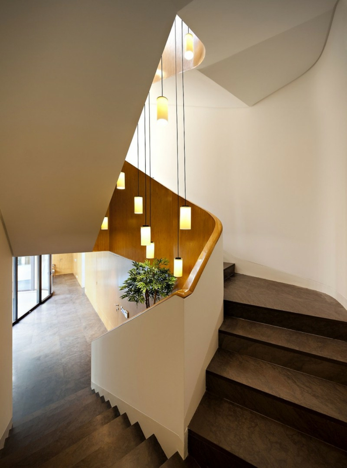 braune Treppe mit weißem Geländer und hängende Lampen, grüne Pflanze